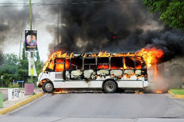 1261729-a-burning-bus-set-alight-by-cartel-gunmen-to-block-a-road-is-pictured-during-clashes-with-federal-fo